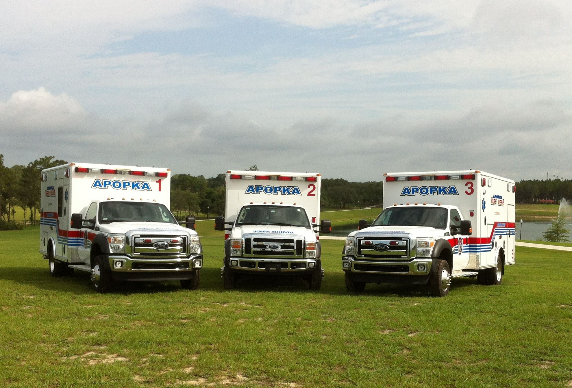Three Apopka ambulance trucks parked on the grass.
