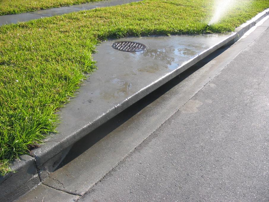 A street drain on a sidewalk.
